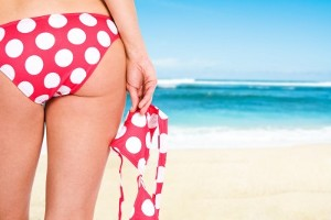 A bikini-bottomed woman's backside and thighs, with the beach and sea in the background