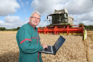 A farmer with a laptop in front of a combine harvester