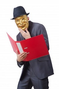 A masked man in a grey suit and hat holding an open ring file